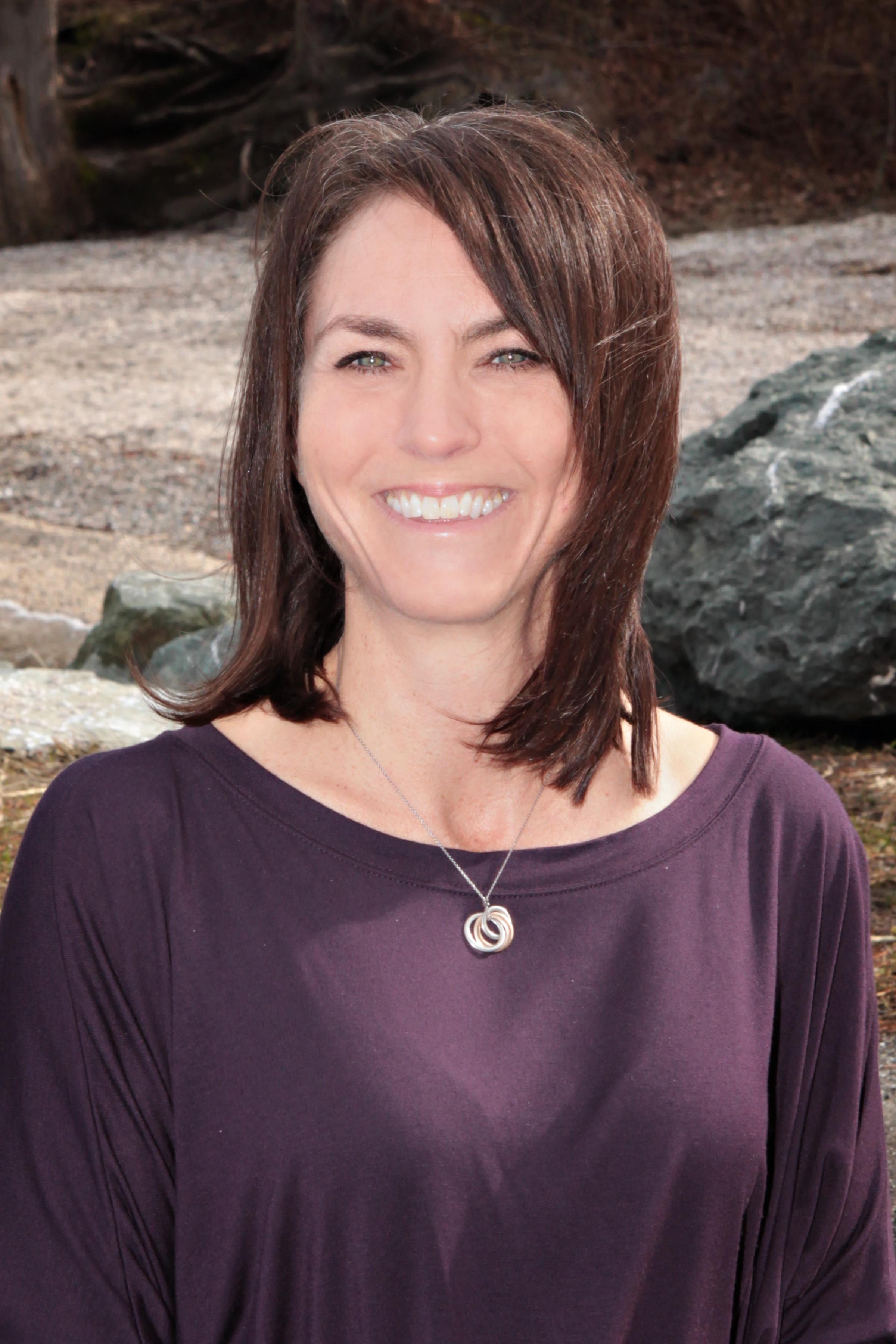 Angela Beaupain in front of rocks wearing a purple shirt