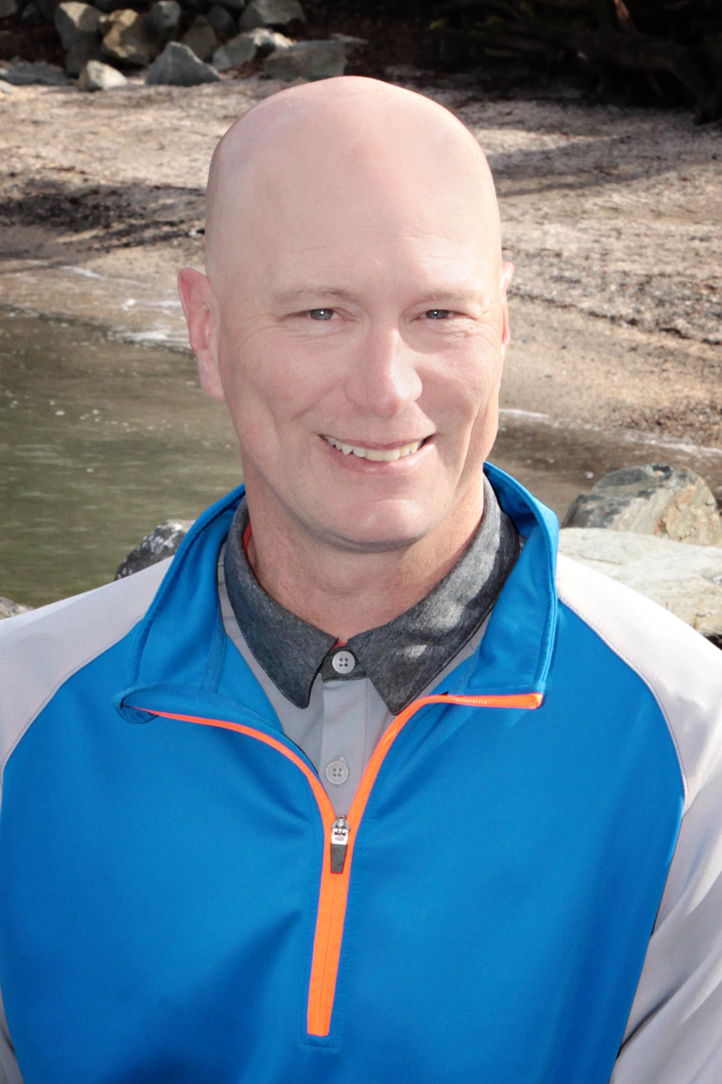 Brian Weeda at the beach wearing a blue jacket