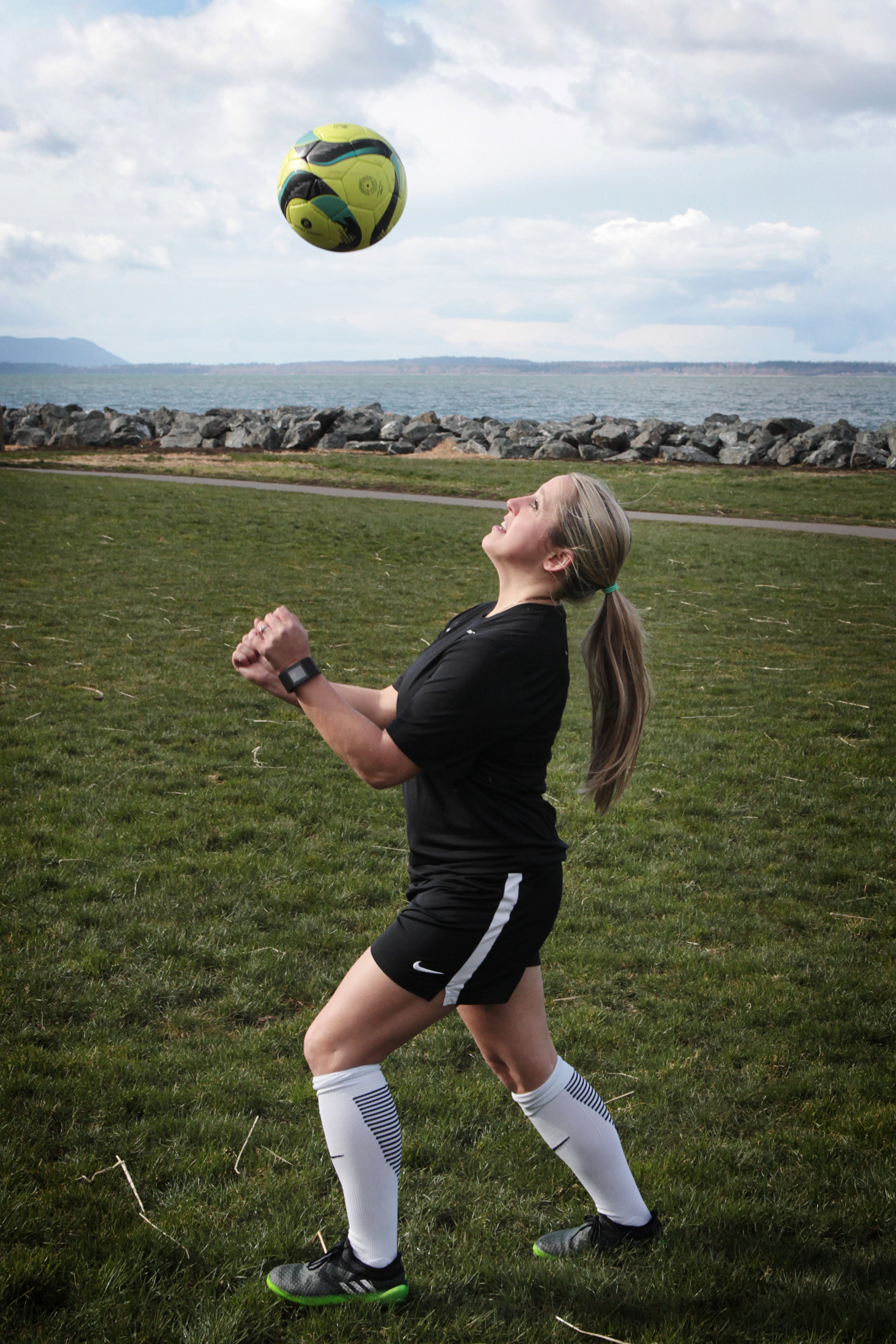 Molly Fossum with a soccer ball above her head