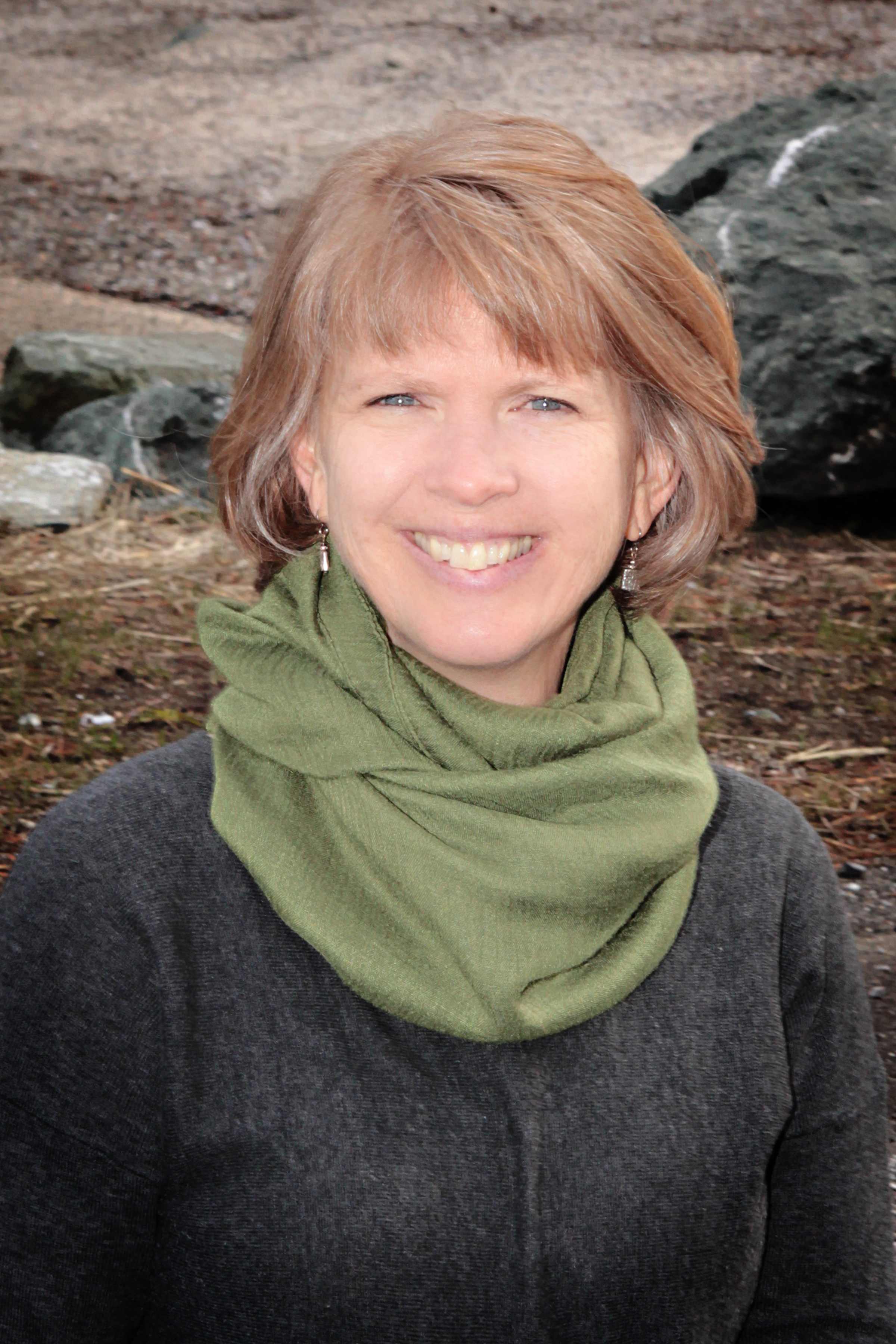 Brenda Henoch in front of rocks wearing a green scarf and gray sweater