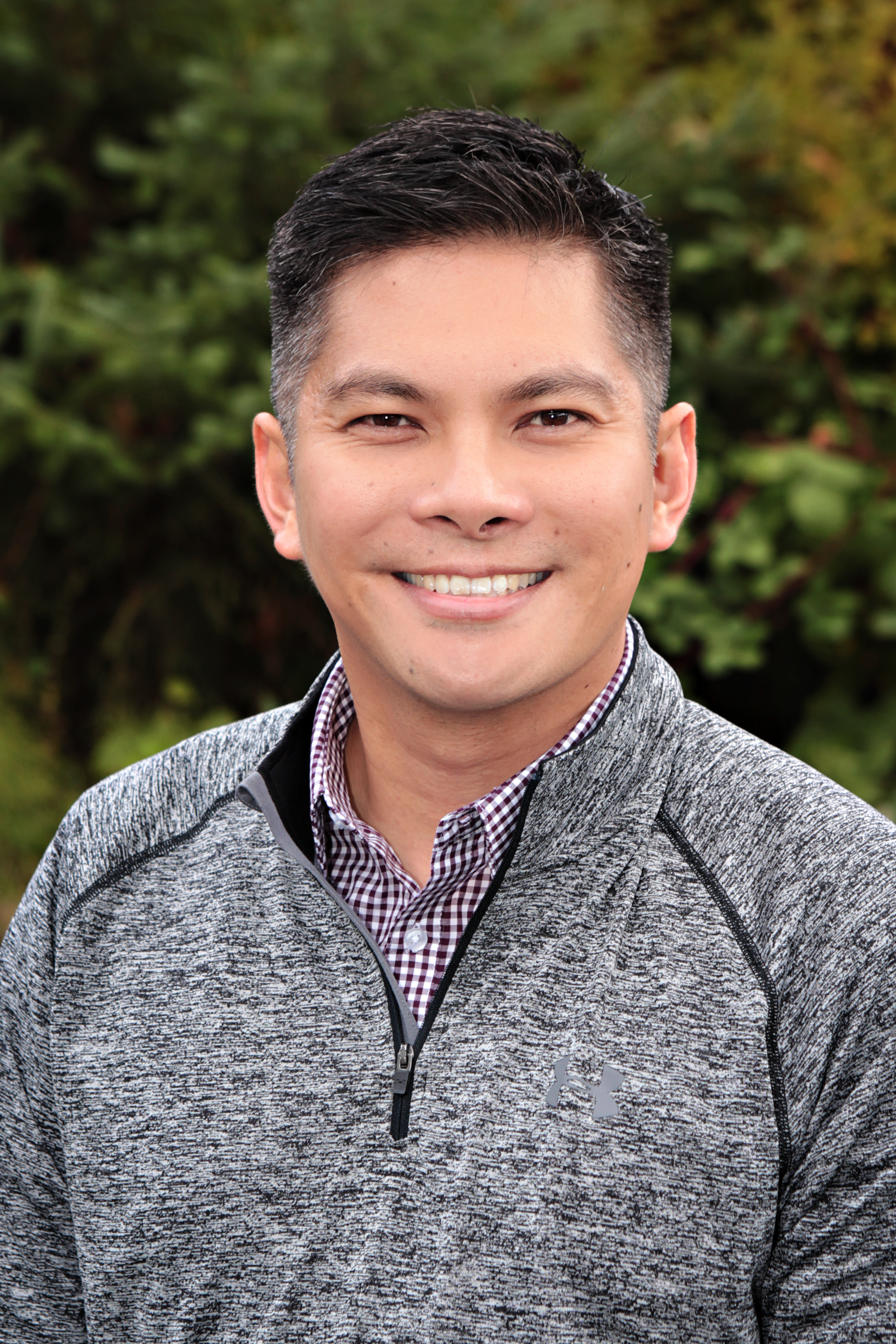 Mark Jamantoc in front of trees wearing a gray jacket